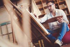 Retrato do artista masculino Working On Painting no estúdio fotografia de stock