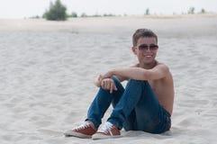Retrato do assento adolescente na areia Fotos de Stock