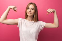 Retrato do bíceps de dobra da moça alegre no fundo cor-de-rosa, bonito e atrativo, fotos de stock