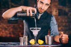 Retrato do barman bonito que usa ferramentas da barra para cocktail alcoólicos Margarita com tequila, fatia de limão e gelo Imagem de Stock Royalty Free