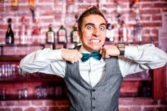 Retrato do barman ou do empregado de bar irritado e forçado com bowtie Imagem de Stock