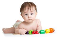 Retrato do bebê bonito com os brinquedos de madeira desenvolventes imagem de stock