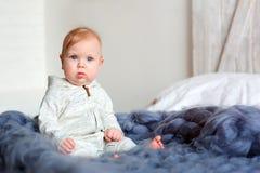 Retrato do bebê bonito do bebê de oito meses que senta-se na cama na cobertura feita malha de tamanho grande Fotografia de Stock Royalty Free