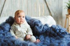 Retrato do bebê bonito do bebê de oito meses que senta-se na cama na cobertura feita malha de tamanho grande Foto de Stock Royalty Free