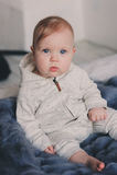 Retrato do bebê bonito do bebê de oito meses que senta-se na cama na cobertura feita malha Imagens de Stock