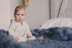 Retrato do bebê bonito do bebê de oito meses que senta-se na cama na cobertura feita malha Fotos de Stock Royalty Free