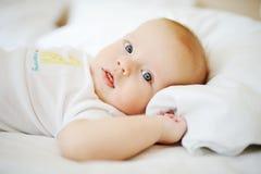 Retrato do bebê com olhos azuis Uma criança que descansa em uma cama Fotografia de Stock