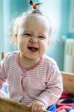 Retrato do bebê de sorriso pequeno adorável que fica em sua cama Imagem de Stock