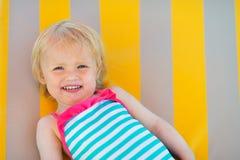 Retrato do bebê feliz que coloca na cama do sol Fotos de Stock Royalty Free