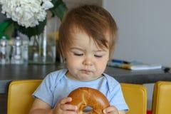 Retrato do bebê pequeno bonito que guarda o bagel em suas mãos e que olha o cèptica com expressão engraçada da cara Imagem de Stock Royalty Free