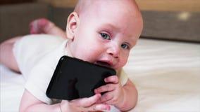 Retrato do bebê que está olhando na câmera e está mastigando o smartphone preto filme