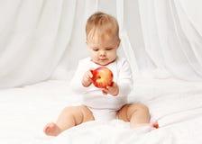Retrato do bebê que senta-se com a maçã vermelha na cama Fotos de Stock