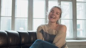 Retrato do blonde de sorriso Uma jovem mulher bonita olha a câmera e ri Mostra seu polegar e inclina sua cabeça vídeos de arquivo