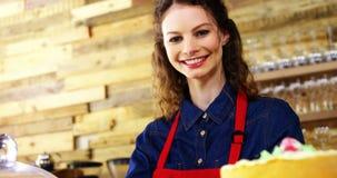 Retrato do bolo de sorriso da terra arrendada da empregada de mesa no contador vídeos de arquivo