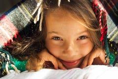Retrato do bom dia do olhar de sorriso encaracolado bonito da menina da escola para fora da manta morna fotografia de stock