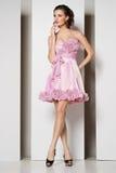 Brunette bonito novo no vestido cor-de-rosa no branco Imagem de Stock