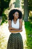Retrato do busto da menina africana bonita macia com as sombras para os olhos verdes que olham de lado no ensolarado borrada Imagem de Stock