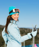 Retrato do busto do esquiador fêmea com os esquis nas mãos fotografia de stock