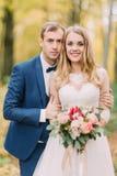 Retrato do busto do noivo que abraça a noiva com a parte traseira do ramalhete do casamento Composição do outono imagens de stock royalty free