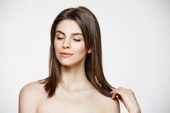 Retrato do cabelo tocante de sorriso da menina bonita moreno nova sobre o fundo branco Beleza dos termas saudável e Fotografia de Stock Royalty Free