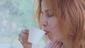 Retrato do café bebendo da mulher bonita nova no movimento lento filme