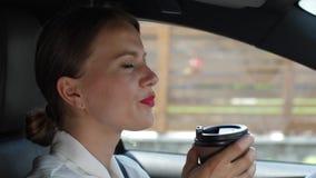 Retrato do café bebendo fêmea que conduz o carro vídeos de arquivo