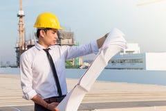 Retrato do capacete de segurança amarelo do desgaste do arquiteto e para verificar o modelo com compromisso no canteiro de obras  imagem de stock royalty free