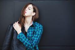 Retrato do casaco de cabedal vestindo da menina moreno que está fora na cidade contra a parede urbana preta Foto de Stock Royalty Free