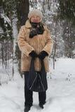 Retrato do casaco de pele superior e do chapéu da mulher que levantam-se na floresta coberto de neve do inverno frio, fim Foto de Stock