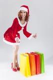 Retrato do Caucasian de sorriso Ginger Santa Helper Girl dos jovens com sacos de compras coloridos Foto de Stock
