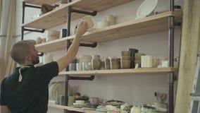 Retrato do ceramist masculino novo, que está escolhendo a caneca a decorar em seu estúdio filme