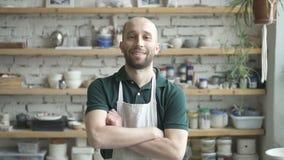 Retrato do ceramist masculino, que está estando em seu estúdio e está olhando à câmera, movimento lento filme