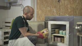 Retrato do ceramist masculino, que está tomando a caneca longe da estufa após o cozimento vídeos de arquivo