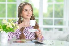 Retrato do chá bebendo da menina bonito ao ler o compartimento imagens de stock