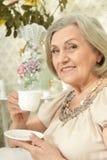Retrato do chá bebendo da mulher superior feliz ao descansar em casa imagens de stock royalty free