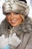 Retrato do chapéu forrado a pele e do revestimento desgastando de mulher nova Foto de Stock