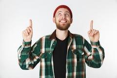 Retrato do chapéu do homem alegre e da camisa de manta vestindo que sorriem, ao apontar os dedos isolados para cima sobre o fundo imagens de stock