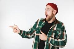 Retrato do chapéu do homem unshaved novo e da camisa de manta vestindo que sorriem, ao apontar os dedos isolados de lado sobre o  foto de stock