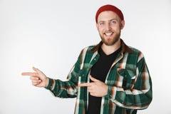 Retrato do chapéu do indivíduo farpado novo e da camisa de manta vestindo que sorriem, ao apontar os dedos isolados de lado sobre fotos de stock