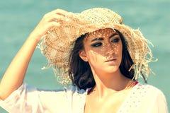 Retrato do chapéu vestindo do verão da jovem mulher bonita na praia Menina do retrato do close up com chapéu de palha foto de stock royalty free