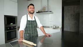 Retrato do chefe de cozinha caucasiano consider?vel novo no avental Ele que fica na cozinha espa?oso moderna de Lighty vídeos de arquivo