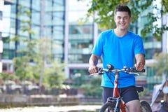 Retrato do ciclismo do homem novo ao lado do rio no ajuste urbano Imagem de Stock Royalty Free