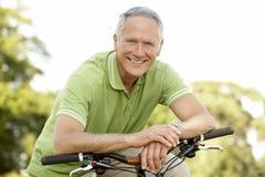 Retrato do ciclo da equitação do homem no campo Foto de Stock Royalty Free