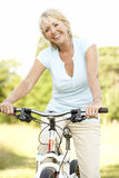Retrato do ciclo maduro da equitação da mulher no countrysi imagem de stock royalty free