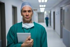 Retrato do cirurgião masculino que está com a tabuleta digital no corredor imagem de stock