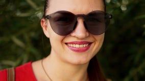 Retrato do close-up do óculos de sol vestindo morenos A menina sorri, seus bordos é batom vermelho menina que anda no parque filme