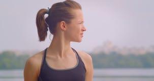 Retrato do close up do basculador fêmea bonito novo no sportswear que olha para a frente com o céu azul no ar livre do fundo filme