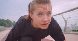 Retrato do close up do basculador fêmea desportivo motivado novo em uma camisa preta de t que senta-se em uma posição de começo e filme
