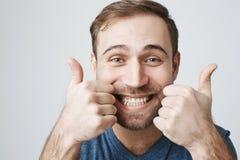 Retrato do close-up do cliente masculino farpado de cabelo escuro com sorriso largo, demonstrando os dentes brancos, olhando foto de stock