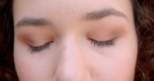 Retrato do close up da cara fêmea caucasiano encaracolado de cabelos compridos nova com os olhos que olham a câmera com luz do so filme